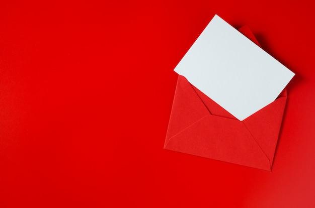 Sobre rojo con papel blanco en blanco. fondo de san valentín maqueta de carta de amor.