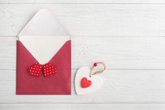 Sobre rojo con papel vacío y corazones rojos