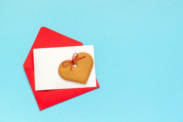 Sobre rojo y tarjeta en blanco para el texto y las galletas en forma de corazón del jengibre en fondo azul.