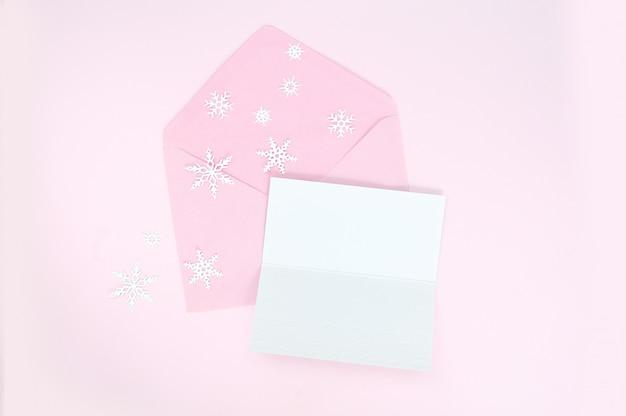 Sobre rosa abierto con copos de nieve de navidad y hoja de papel en blanco