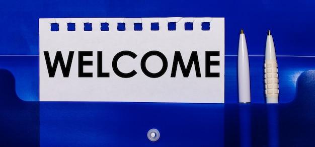 Sobre una superficie azul, bolígrafos blancos y una hoja de papel con el texto bienvenido