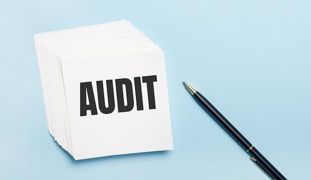 Sobre una superficie azul claro, hay un bolígrafo negro y una pila de papel de notas blanco con el texto audit.
