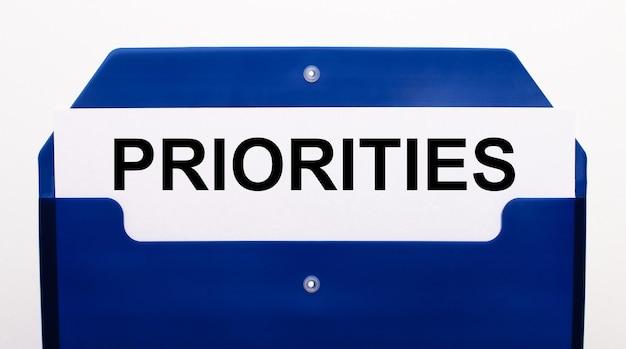 Sobre una superficie blanca, una carpeta azul para papeles. en la carpeta hay una hoja de papel con la palabra prioridades