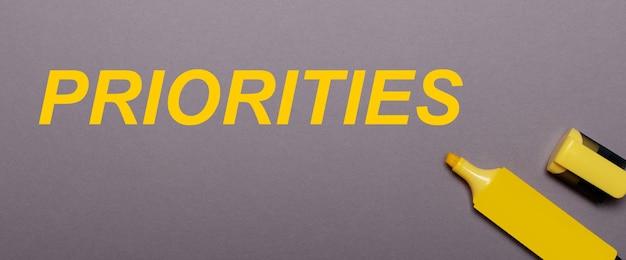 Sobre una superficie gris, rotulador amarillo e inscripción amarilla prioridades
