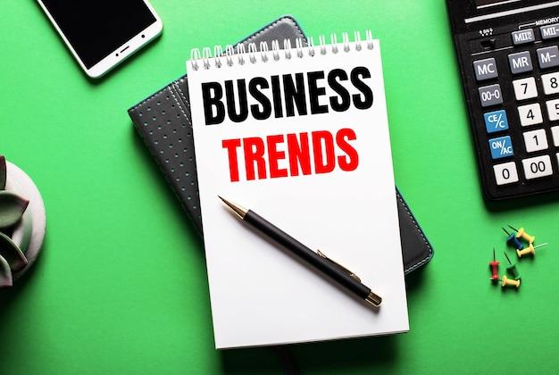 Sobre una superficie verde un teléfono, una calculadora y un diario con la inscripción tendencias empresariales