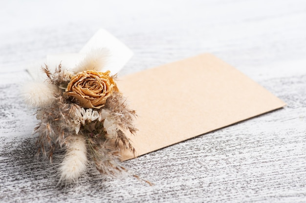 Sobre vacío de papel y kraft con ramo de flores secas de colores neutros. simulacros de boda en mesa blanca