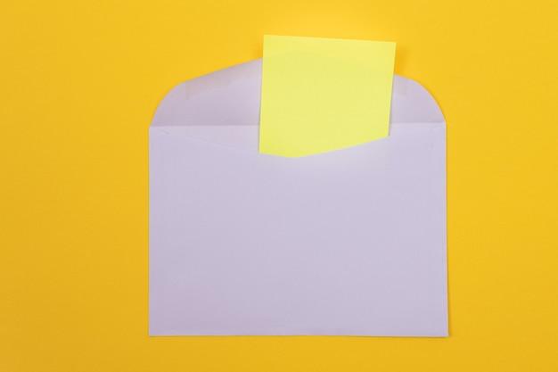 Sobre violeta con hoja de papel amarillo en blanco dentro