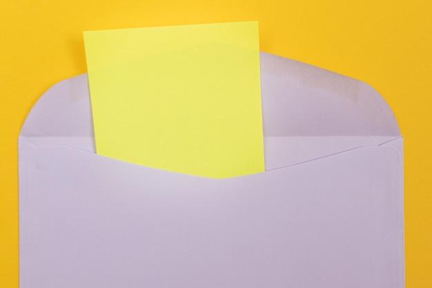 Sobre violeta con hoja de papel amarillo en blanco en el interior acostado sobre fondo amarillo simulacro con cop ...