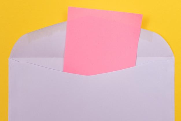 Sobre violeta con hoja de papel rosa en blanco dentro