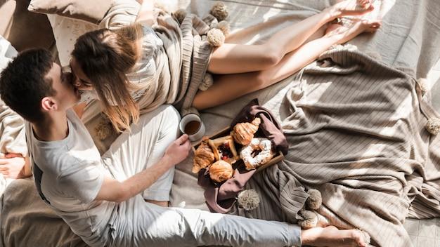 Una sobrecarga de una joven pareja besándose mientras desayunan en la cama