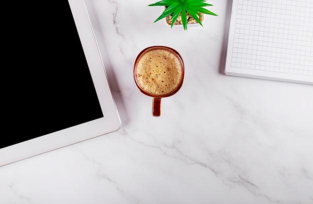 Sobrecarga de mesa de oficina con café, bloc de notas y tableta, negocios en el lugar de trabajo