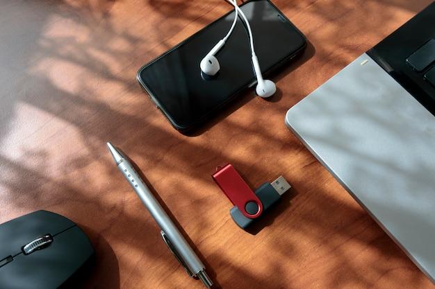 Sobrecarga de la mesa de oficina con laptop, mouse, teléfono inteligente, usb. las herramientas de escritorio de trabajo de oficina muestran un tono vintage con espacio de copia.