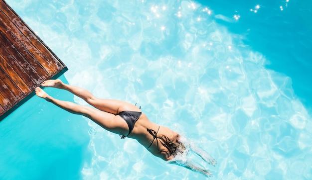 Sobrecarga de mujer buceando en la piscina