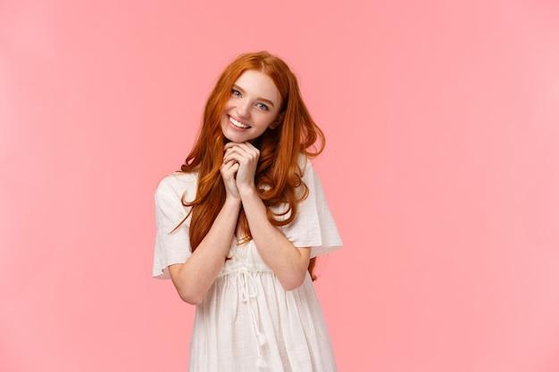 Sobrecarga de ternura. chica europea tonta pelirroja kawaii con mirada encantadora y sonrisa, inclinando la cabeza, rogando algo, pidiendo comprar algo lindo en la tienda, sonriendo alegre, de pie rosa