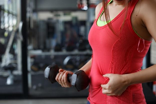 Sobrepeso vientre graso de mujer y sosteniendo una pesa.