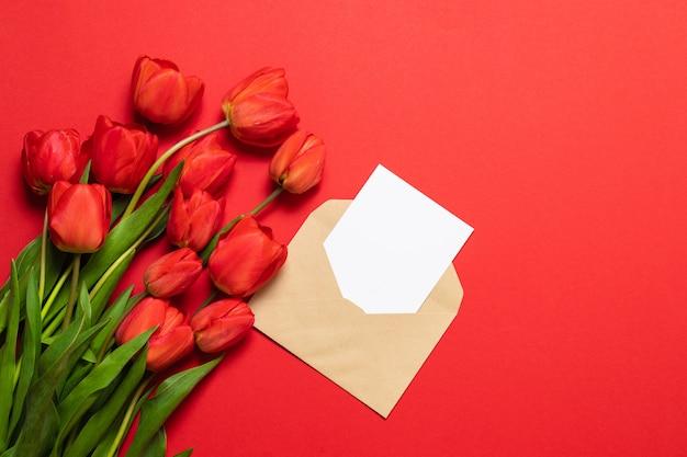 Sobres con espacio para texto y hermosos tulipanes rojos sobre un fondo rojo. cerca