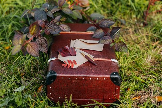 Sobres de papel artesanal y pluma estilográfica dorada en la maleta vintage