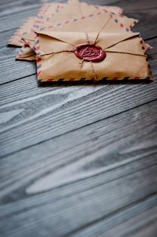 Sobres retro vintage antiguos con un sello de cera en la vieja mesa de madera de color marrón oscuro