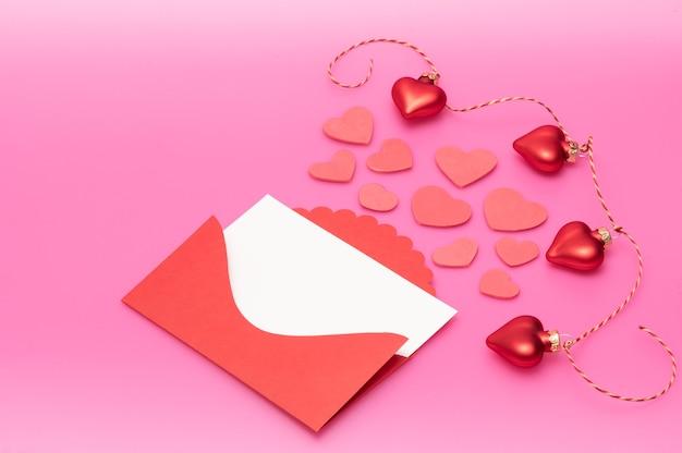 Sobres rojos con membrete blanco para texto y decoración en forma de corazones en una cuerda