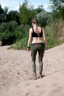 Sobrevivir y viajar concepto. mujer blanca flaca, vestida con traje militar, caminando por la orilla arenosa del río, vista desde atrás.