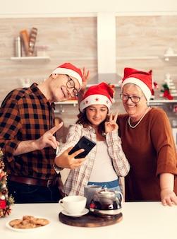 Sobrina tomando selfie con abuelos celebrando la navidad