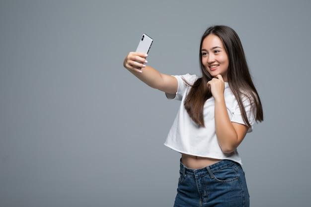 Sociable hermosa chica asiática tomando selfie o hablando en video llamada usando un teléfono celular sobre fondo gris