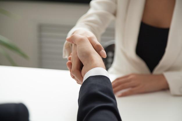 Socio de saludo del trabajador de sexo femenino con el apretón de manos