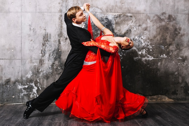 Socios bailando sensual baile cerca de la pared gris