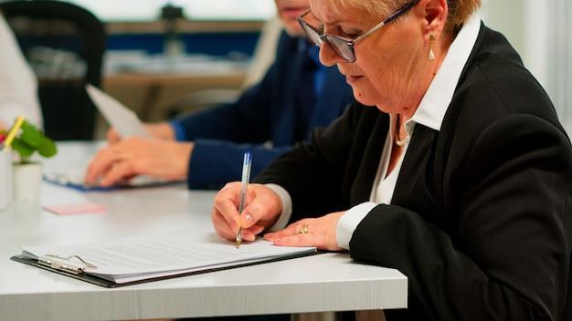 Socios de busiess que discuten un nuevo proyecto para la evolución de la empresa, una mujer de alto nivel que verifica las tareas en el portapapeles y firma un nuevo contrato. junta de accionistas del director ejecutivo en la oficina de puesta en marcha