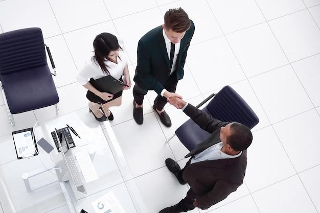 Los socios comerciales del apretón de manos en una reunión de negocios
