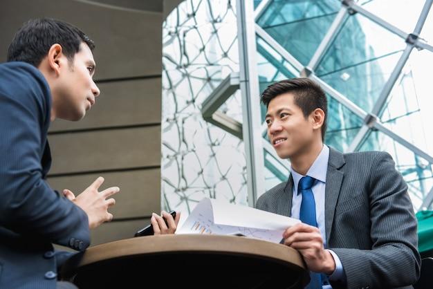 Socios comerciales asiáticos jovenes que discuten el trabajo