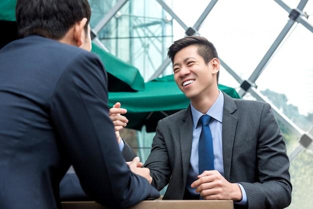 Socios comerciales asiáticos jovenes que hablan en el café