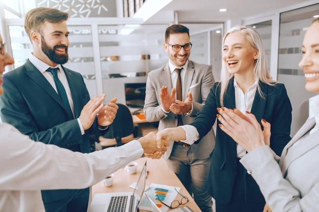 Socios comerciales dándose la mano mientras otros colegas aplauden.