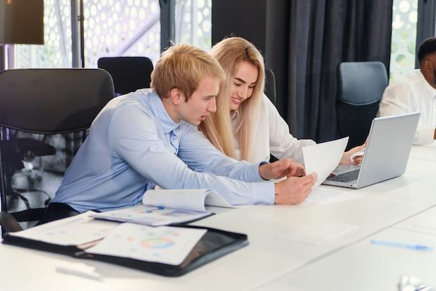 Socios comerciales decididos y agradables que estudian cuidadosamente documentos financieros con gráficos en la mesa de la sala de juntas en la sala de reuniones.