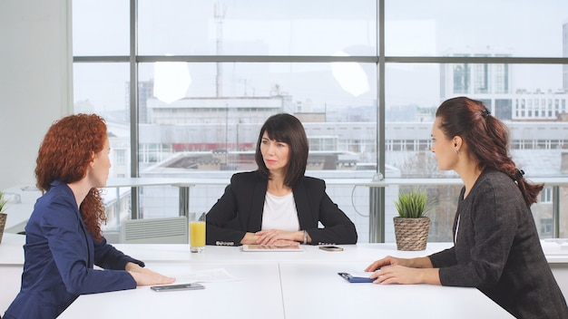 Socios comerciales decididos que estudian activamente documentos comerciales en una mesa de conferencia de madera