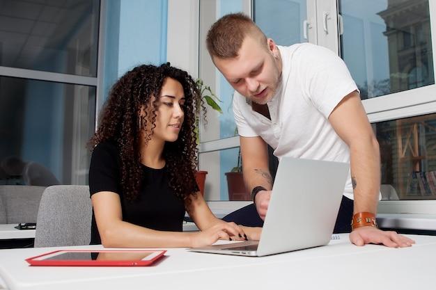 Socios comerciales discutiendo junto a una computadora portátil