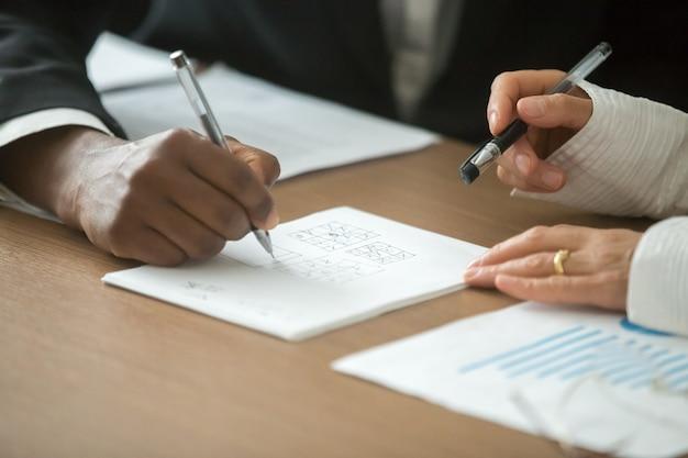 Socios comerciales diversos que juegan el juego del tic-tac-toe en el escritorio de oficina, primer