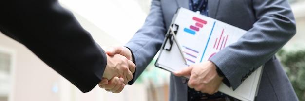 Socios comerciales estrecharme la mano en primer plano de la conferencia