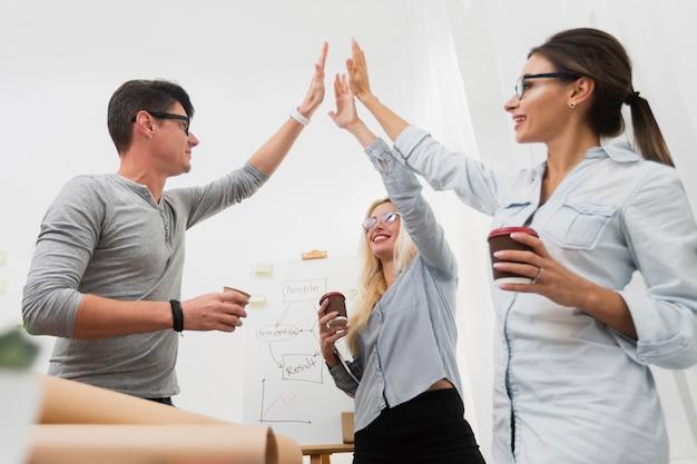 Socios comerciales felices levantando las manos