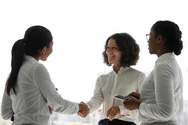 Socios comerciales femeninos felices celebrando contrato exitoso