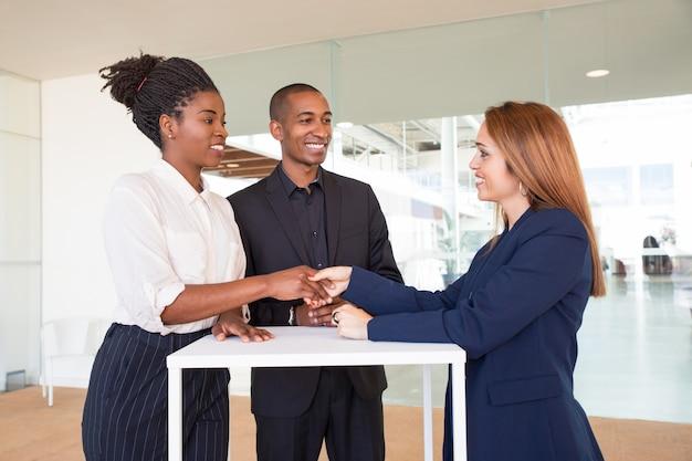 Socios comerciales femeninos positivos que sacuden las manos