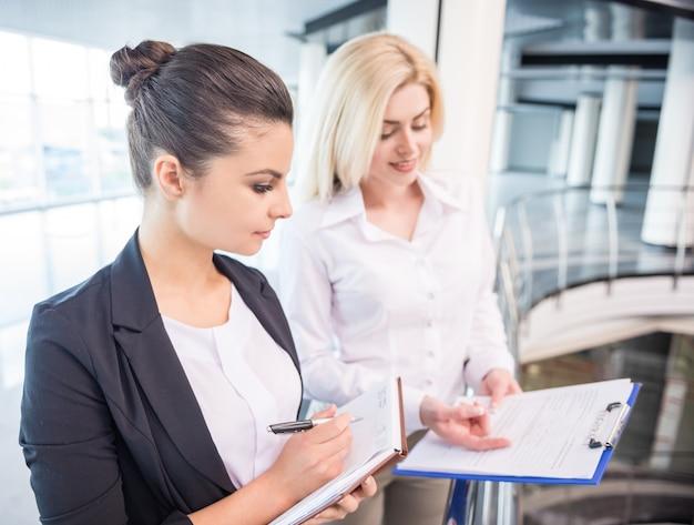 Los socios comerciales femeninos vestidos formales discuten proyecto.