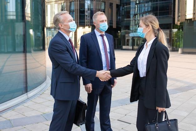 Socios comerciales en máscaras faciales haciendo trato o saludo. empresaria exitosa profesional y empresarios de pie al aire libre y apretón de manos. concepto de negociación, protección y asociación