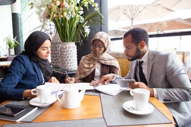 Socios comerciales multiculturales discutiendo contrato en café