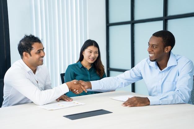Los socios comerciales multiétnicos felices comienzan la colaboración después de la negociación.