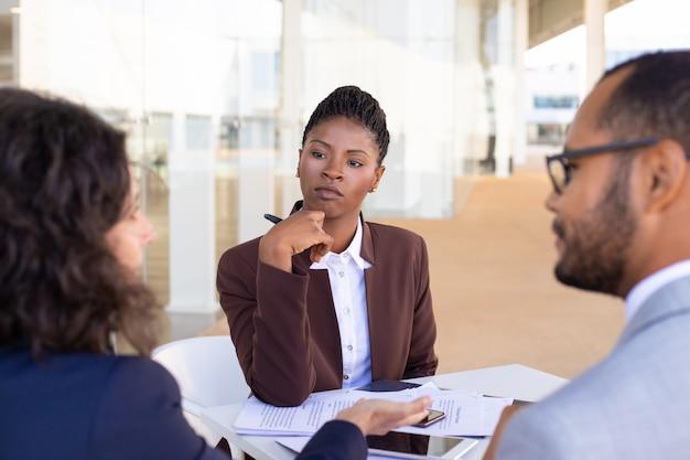 Socios comerciales multiétnicos que discuten los términos del contrato