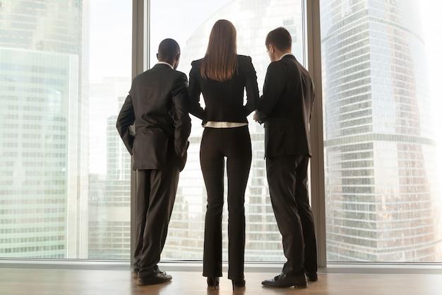 Socios comerciales multinacionales de pie juntos