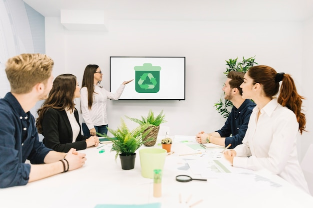 Socios comerciales que miran al encargado de sexo femenino que presenta con el icono del reciclaje en la pantalla