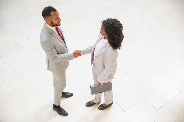 Socios comerciales que se saludan en el pasillo de la oficina