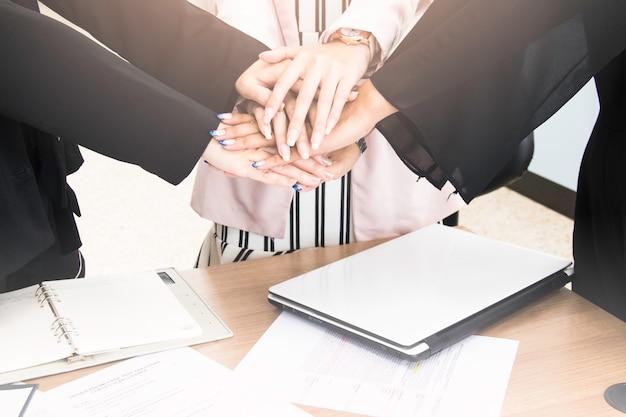 Socios comerciales que unen sus manos después de que el contrato finaliza la reunión.